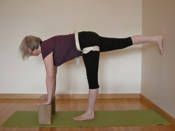 preparation for half-moon pose, foot to wall, strap to standing leg thigh