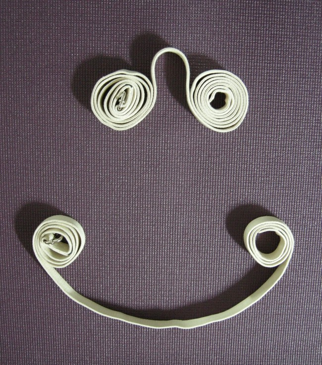 a happy face in yoga straps