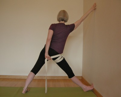 full pose of triangle at the wall with strap to the right thigh