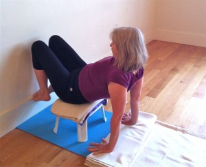 shoulder stand preparation on a little plastic stool five
