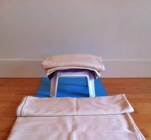 shoulder stand preparation on a little plastic stool five